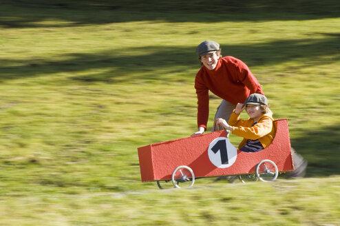 Austria, Salzburger Land, Man and boy (12-13)  with soapbox car, having fun - HHF02939