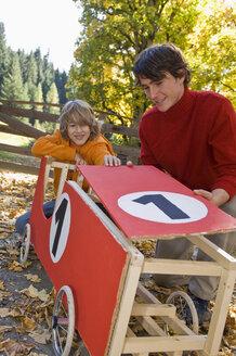 Austria, Salzburger Land, Man and boy (12-13) looking at soapbox car - HHF02929