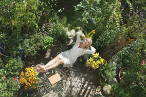 Austria, Salzburger Land, Young woman in garden, relaxing, elevated view - HHF02860