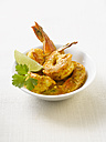 King prawns in curry marinade with lemon slices on plate - KSWF00477