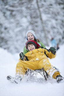 Germany, Bavaria, Siblings (8-9) sledding downhill, laughing - MAEF01757