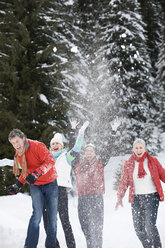 Italy, South Tyrol, Seiseralm, Four persons throwing snow in the air - WESTF11495