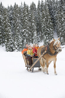Italy, South Tyrol, Seiseralm, Family riding in sleigh - WESTF11480
