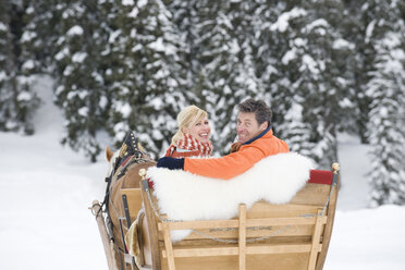 Italy, South Tyrol, Seiseralm, Couple in sleigh, smiling, portrait - WESTF11474