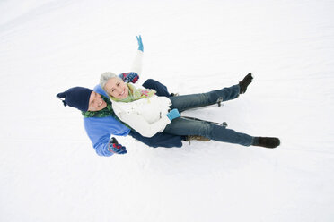 Italy, South Tyrol, Seiseralm,   Senior couple sledding down hill, laughing, portrait - WESTF11450