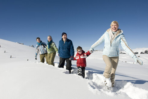 Italy, South Tyrol, Seiseralm, Family walking in snow - WESTF11426
