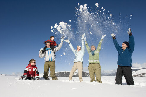 Italy, South Tyrol, Seiseralm, Family cheering in snow - WESTF11423