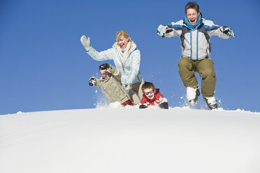 Italy, South Tyrol, Seiseralm, Family jumping in snow - WESTF11411
