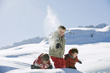 Italy, South Tyrol, Seiseralm, Children throwing snow in the air - WESTF11405