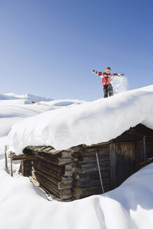 Italy, South Tyrol, Seiseralm, Boy (4-5) standing on snow-covered roof of log cabin - WESTF11399