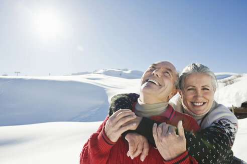 Italy, South Tyrol, Seiseralm, Senior couple embracing in winter scenery, portrait, close-up - WESTF11387