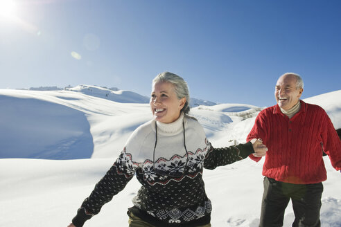 Italy, South Tyrol, Seiseralm, Senior couple in winter scenery - WESTF11384
