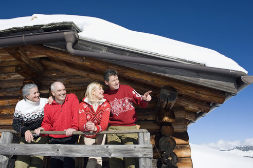 Italy, South Tyrol, Seiseralm, Log Cabin, Couple standing on balcony - WESTF11360