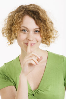 Young woman with finger on her lips, portrait - CLF00794