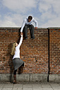 Germany, Bavaria, Munich, Young man helping young woman to climb a wall - RBF00088