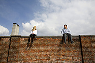 Germany, Bavaria, Munich Young couple sitting on top of brick wall - RBF00082
