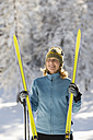 Austria,Tyrol, Seefeld, Wildmoosalm, Woman holding cross-country skis - MIRF00009