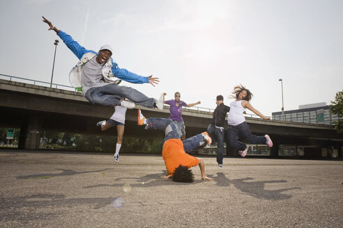 Germany, Cologne, Group of people breakdancing on street - SK00033