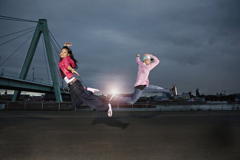 Germany, Cologne, Man and woman jumping, Skyline in background - SK00015
