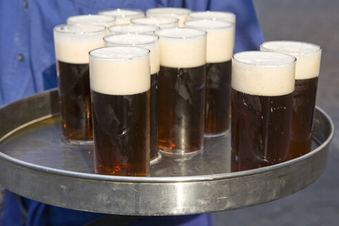 Germany, Waiter holding tray with beer glasses - WDF00543