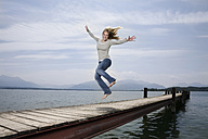 Germany, Chiemsee, Woman jumping on jetty - RBF00104