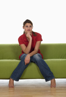 Young woman on sofa looking sceptical, portrait - WWF00910