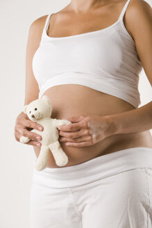 Pregnant woman holding teddy, mid section - LDF00699
