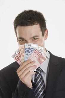 Businessman holding Euro notes, portrait - LDF00727