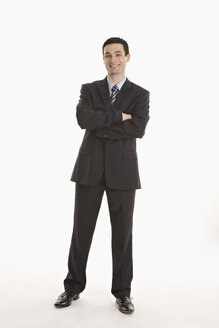 Businessman standing with arms crossed, smiling, portrait - LDF00724