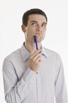 Businessman holding pen, looking up, portrait - LDF00721