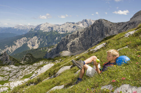 Germany, Garmisch-Partenkirchen, Alpspitz, Boy (10-11) lying on meadow, holding apple, side view, portrait - RNF00013