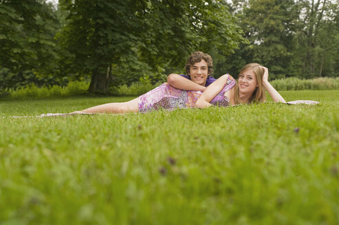 Germany, Bavaria, Starnberger See, Young couple lying in meadow - RNF00033