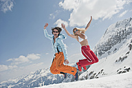 Austria, Salzburger Land, Young couple jumping in air, laughing, portrait - HHF03071
