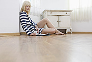 Germany, Berlin, Young woman sitting on floor, portrait - WESTF13481