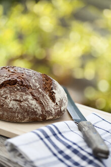 Loaf of farmhouse bread on wooden table - MAEF01862