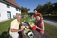 Germany, Bavaria, People at table in garden preparing food - WESTF13265