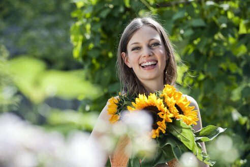 Germany, Bavaria, Woman holding bunch of sunflowers, smiling, portrait - WESTF13247