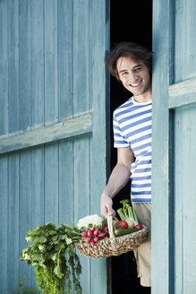 Germany, Bavaria, Man in front of barn door holding basket with fresh vegetables, smiling, portrait - WESTF13226