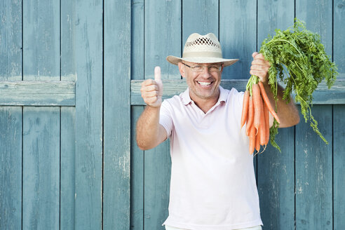 Germany, Bavaria, Man in front of barn door holding bunch of carrots, smiling, portrait - WESTF13223