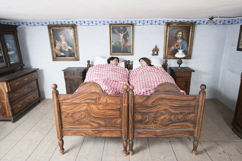 Germany, Bavaria, Young couple lying in bedroom - WESTF13205