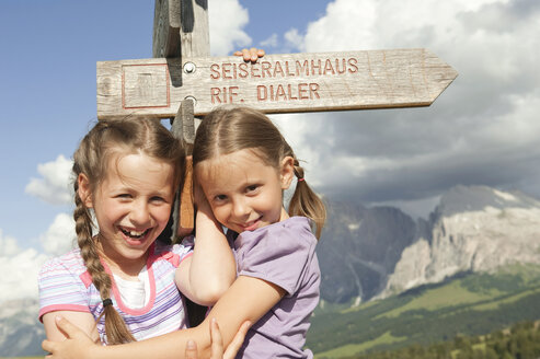Italy, Seiseralm, Girls (6-7), (8-9) standing by sign post, smiling, portrait, close-up - WESTF13435