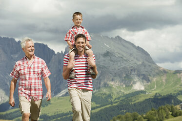 Italy, Seiseralm, Grandfather, Father and son (6-7) walking in meadow, smiling, portrait - WESTF13396