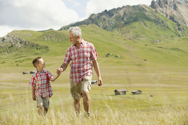 Italy, Seiseralm, Grandfather and grandson (6-7) walking in field - WESTF13390