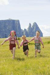 Italy, Seiseralm, Three children (4-5), (6-7), (8-9) running in field - WESTF13387