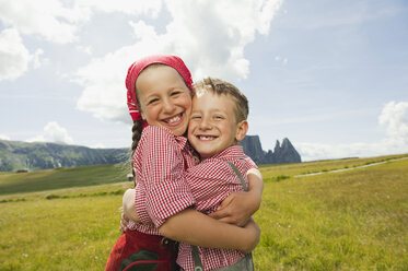 Italy, Seiseralm, Boy (6-7) and girl (8-9) in field, embracing, smiling, portrait - WESTF13384