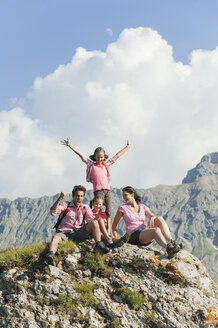 Italy, South Tyrol, Family sitting on rock, cheering, portrait - WESTF13714
