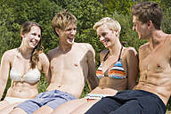 Germany, Bavaria, Young people in swimwear, side by side, smiling, portrait, close-up - LDF00800