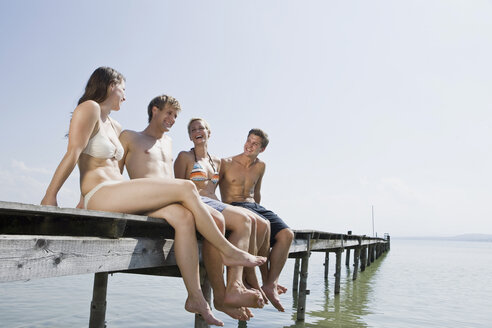 Germany, Bavaria, Ammersee, Young people sitting on jetty, smiling, portrait - LDF00776