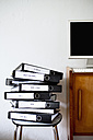 Folders stacked on stool, in background monitor and computer - JRF00129