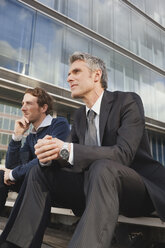 Germany, Hamburg, Two businessmen sitting on steps in front of office building - WESTF13892